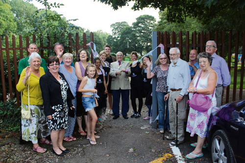 Yate mayor Tony Davis joins Nicole Jones and Suzanne Jenkinson for the opening of the gate linking the Vintage Birdcage Cakery with Kingsgate Park, flanked by Yate town councillors and members of the Friends of Kingsgate Park.